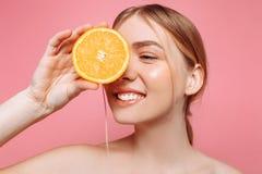 Portret van een vrouwelijk meisje, een natuurlijk zuiver meisje met een halve sinaasappel, die één oog behandelen met een sinaasa royalty-vrije stock afbeeldingen