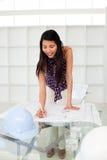 Portret van een vrouwelijke architect die plannen bestudeert stock afbeelding