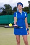 Portret van een vrouwelijke speler die een tennisbal op haar racket houden Royalty-vrije Stock Afbeeldingen