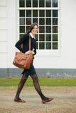 Portret van een vrouwelijke student die in openlucht met zak lopen Stock Fotografie