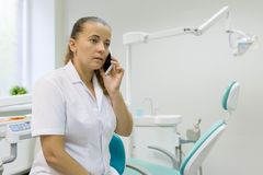 Portret van een vrouwelijke tandarts, arts die op mobiele telefoon op tandstoelachtergrond spreken Geneeskunde, tandheelkunde en  royalty-vrije stock afbeelding