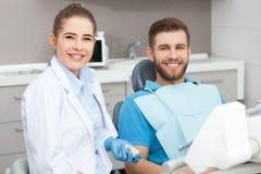 Portret van een vrouwelijke tandarts en een jonge mens in een tandartsbureau stock fotografie