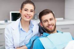 Portret van een vrouwelijke tandarts en een jonge mens in een tandartsbureau royalty-vrije stock fotografie