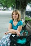 Portret van een vrouwenzitting op middelbare leeftijd op een bank stock foto's