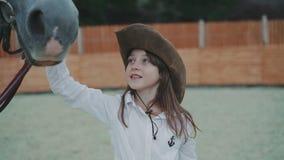 Portret van een weinig gelukkig meisje die vrij wit paard op het gebied strelen 4K stock footage