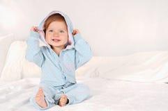 Portret van een weinig glimlachend meisje thuis gekleed in blauwe pyjama's Royalty-vrije Stock Afbeelding