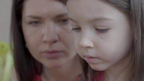 Portret van een weinig leuk mooi meisje die onderwijsspel dicht omhoog spelen Haar moeder helpt het kind, die haar adviseren stock video