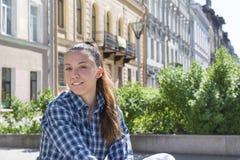 Portret van een wit meisjesclose-up op de straat, de voorgevels van stock fotografie