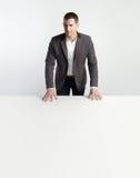 Portret van een zakenman die zich achter lijst bevindt Royalty-vrije Stock Afbeelding
