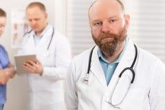 Portret van een zekere echte arts die zich voor zijn gezondheidsteam bevinden royalty-vrije stock afbeeldingen