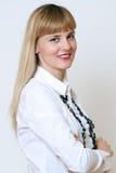 Portret van een zekere jonge bedrijfsdame die zich met gevouwen bevinden Royalty-vrije Stock Foto
