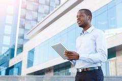 Portret van een zekere jonge zwarte zakenman met tablet stock afbeelding