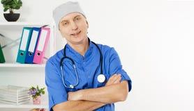 Portret van een Zekere Rijpe die Arts Looking At Camera op Medische Bureauachtergrond wordt ge?soleerd stock foto's