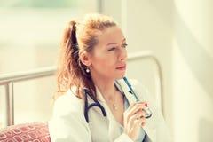 Portret van een zekere vrouw artsenzitting in haar bureau Royalty-vrije Stock Afbeelding