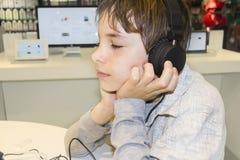 Portret van een zoete jonge jongen die aan muziek luistert Royalty-vrije Stock Afbeeldingen