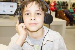Portret van een zoete jonge jongen die aan muziek luistert Stock Fotografie