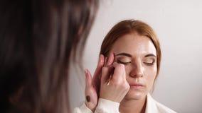 Portret van een zoete vrouw die wordt toegepast op het lagere ooglid met een borstel stock videobeelden