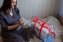 Portret van een zwangere vrouw op het bed met een controlelijst en een zakmensen, de prijzen aan het ziekenhuis royalty-vrije stock afbeelding