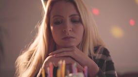 Portret van eenzame droevige meisjeszitting voor weinig cake met aangestoken niet kaarsen De ongelukkige vrouw heeft verjaardagsp stock footage