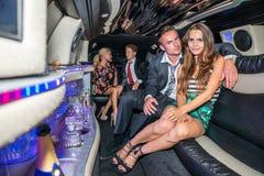 Portret van elegant jong paar met vrienden die in limousi spreken royalty-vrije stock foto's