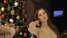 Portret van elegant meisje in avondjurk het stellen voor een spiegel bij Nieuwjaar holibays met Kerstboom Brunette stock video