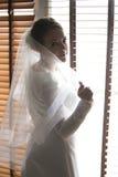 Portret van elegante bruid met het lange sluier stellen bij grote vensterwi Royalty-vrije Stock Fotografie