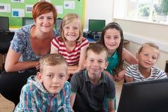 Portret van Elementaire Leerlingen in Computerklasse met Leraar stock afbeelding