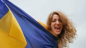 Portret van emotionele jonge verbazende vrouw die blauwe en gele Oekraïense vlag over de hemelachtergrond houden stock video