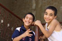 Portret van 2 en jongens die, straatachtergrond in giza, Egypte spelen lachen Stock Foto's