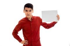 Portret van ernstig jong donkerbruin mannelijk model met aanplakbiljet in handen dat op witte achtergrond wordt geïsoleerd Royalty-vrije Stock Afbeeldingen