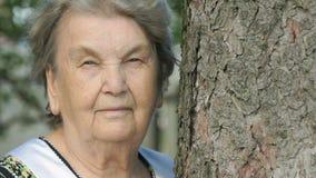 Portret van ernstig oud bejaarde in bos stock video