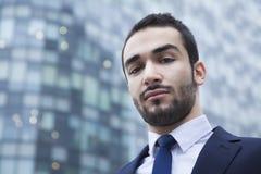 Portret van ernstige jonge zakenman, in openlucht, bedrijfsdistrict Royalty-vrije Stock Afbeeldingen