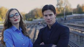 Portret van ernstige partners met gekruiste handen die camera 4K bekijken stock videobeelden