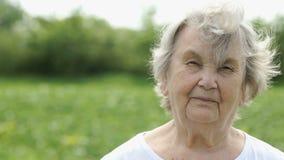 Portret van ernstige rijpe oude vrouw in openlucht stock videobeelden