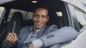 Portret van ernstige zakenmanzitting binnen auto en in openlucht het glimlachen in camera stock foto