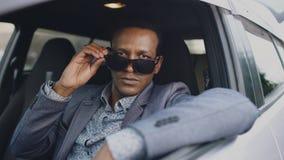 Portret van ernstige zakenmanzitting binnen auto gezet van zonnebril en in openlucht het glimlachen in camera stock foto's
