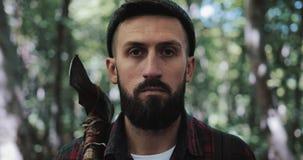 Portret van ernstige zekere houthakker, volwassen gebaarde mens die een grote bijl houden en de camera in openlucht onderzoeken i stock footage