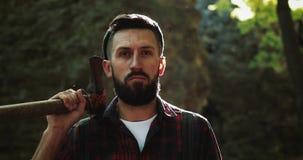 Portret van ernstige zekere houthakker, volwassen gebaarde mens die een grote bijl houden en de camera in openlucht onderzoeken i stock video