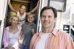 Portret van familie met kampeerautobestelwagen stock foto
