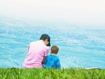 Portret van familiemoeder en babyzoon die samen in aard zitten Stock Foto