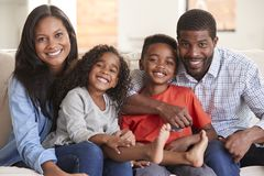Portret van Familiezitting op Sofa At Home Smiling At-Camera stock foto's