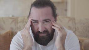 Portret van gebaard masserend zijn hoofd met grote handen met uitdrukking van dicht omhoog het lijden op gezicht De volwassen men stock video