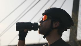 Portret van gebaard triathlete drinkwater van bidon alvorens op te leiden Sluit omhoog om mening Triatlonconcept stock footage