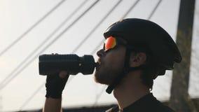 Portret van gebaard triathlete drinkwater van bidon alvorens op te leiden Sluit omhoog om mening Triatlonconcept Langzame Motie stock videobeelden