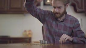 Portret van gebaarde mensenzitting bij de lijst in het keuken tellende geld Beardie in geruit overhemd stapelt dan muntstukken stock video