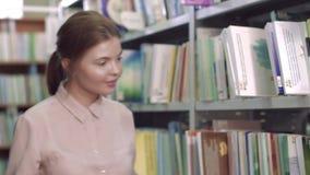 Portret van geconcentreerd universiteitsmeisje die een boek onder boekenkasten zoeken stock footage