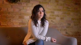 Portret van geconcentreerde Kaukasische donkerbruine vrouwenzitting op bank het letten op film zorgvuldig in comfortabele huisatm stock videobeelden