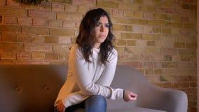 Portret van geconcentreerde Kaukasische donkerbruine vrouwenzitting op bank het letten op thriller zorgvuldig in comfortabele hui stock videobeelden