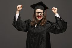 Portret van gediplomeerde volwassen vrouwelijke student in zwarte graduatietoga stock afbeelding