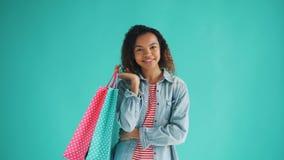 Portret van gelukkig Afrikaans Amerikaans meisje met winkelende zakken tevreden klant stock footage